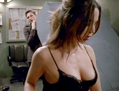 Eliza Dushku in a short leather skirt and black bra showing her cleavage